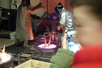 Grabbing the crucible full of molten bronze.