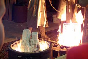 Getting the crucible ready to pour into the heated cast.