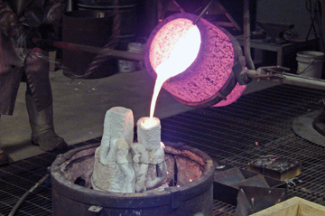 Pouring the molten bronze into the cast.